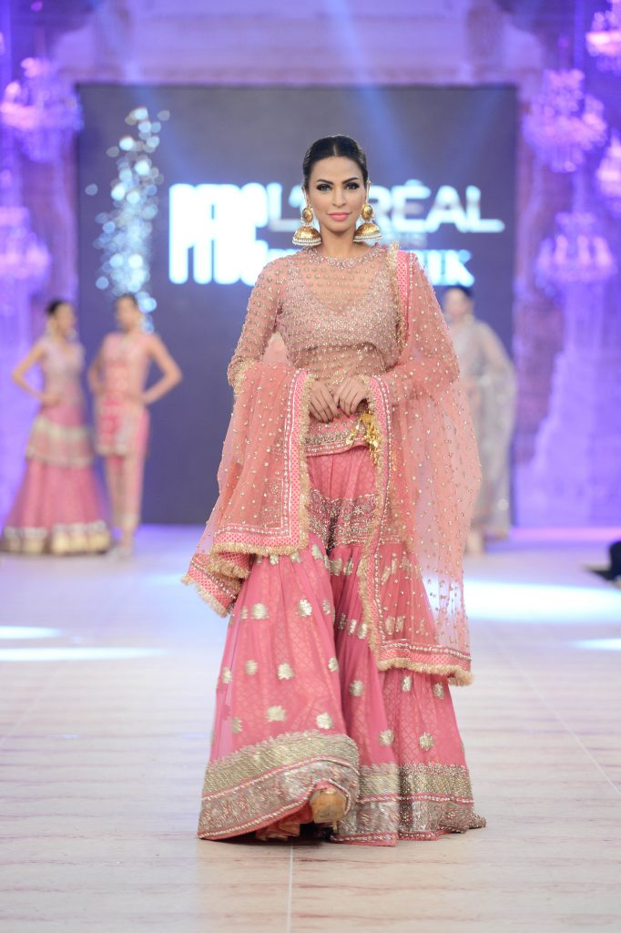 a model in a pink an silver lehenga walking the ramp